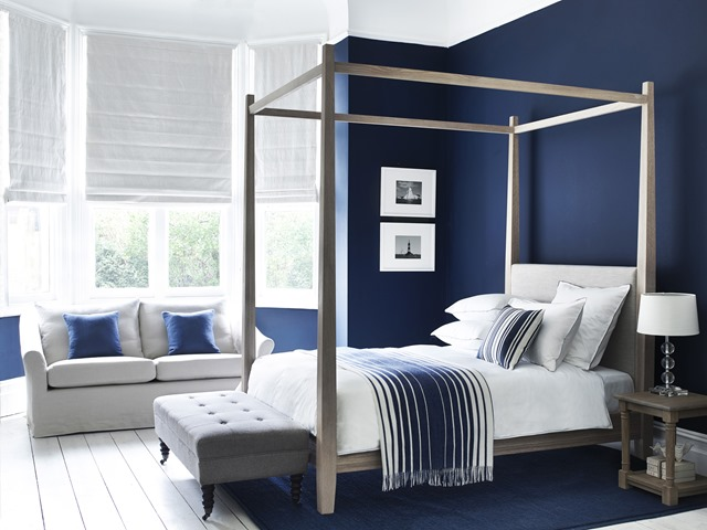 Bold and Beautiful Bedroom: Wardley king size bed in Chalked Oak and Holkham Sand headboard €2,900 (£2,095); Arthur stool in Angus with dark oak legs €580 (£420); Tolsey rug in Navy €485 (£350); Edinburgh side table €345 (£250); Burlington small lamp with Lucile shade in Warm White €165 (£117); Cley throw in Navy Stripe €195 (£140); Grace scatter cushion in Agatha Navy€49 (£35), Sophie bed linen in Peat; Long Island medium sofa in Pale Oat €2,470 (£1,780); Beatrice scatter cushions in Brancaster Navy €49 (£35); Low water prints III and VI; paintwork in Navy. www.neptune.com