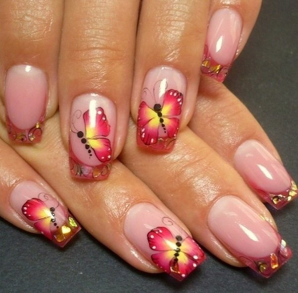 Beautiful marble inspired butterfly nail art. The base of the nails is coated in cream and gray colors depicting a marble like design, as a pair of butterfly wings are painted on either side of the nails as they meet together in the middle.