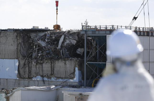 A member of the media, wearing a protective suit and a mask, looks at the No. 3 reactor building at Tokyo Electric Power Co's (TEPCO) tsunami-crippled Fukushima Daiichi nuclear power plant in Okuma town, Fukushima prefecture, Japan in this 10 February 2016 file photo. Photo: Toru Hanai / Reuters