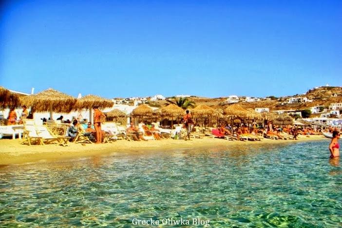 Greckie błękitne morze, bezchmurne wrześniowe niebo, na plaży turyści trzcinowe parasole leżaki