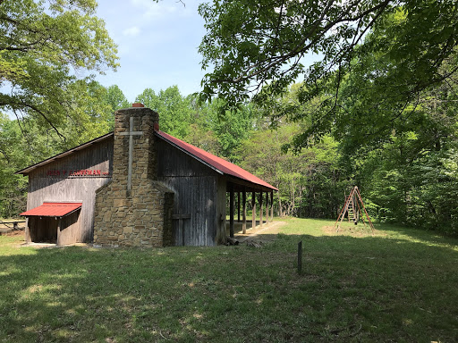 The south end exterior view of the The Jean Kaufmann Memorial Shelter, featuring a large stone fireplace. The shelter is surrounded by tall trees, and both open and shady grassy areas.