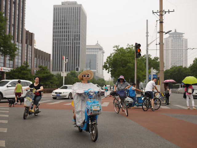 female with a wide-brimmed hat and sunglasses riding a scooter and two others carrying umbrellas on a cloudy day in Beijing