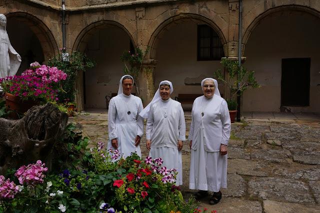 Tres hermanas doroteas posan en el medio de un patio porticado y adyacentes a un conjunto floral coronado por una escultura de la Virgen María.