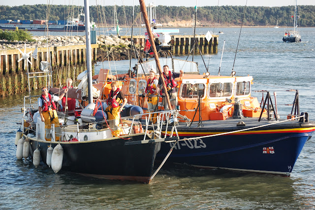 Poole crew smiling at photographer Dave Riley (sorry we left you behind Dave!) as the broken-down yacht is brought into Poole Quay Boat Haven. 22 August 2013 Photo credit: RNLI/Dave Riley