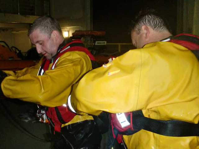 31 May 2012 - Mechanic Paul Taylor helps adjust the straps on Crew Member Scott Rowland's new lifejacket. Photo: RNLI Poole/Dave Riley
