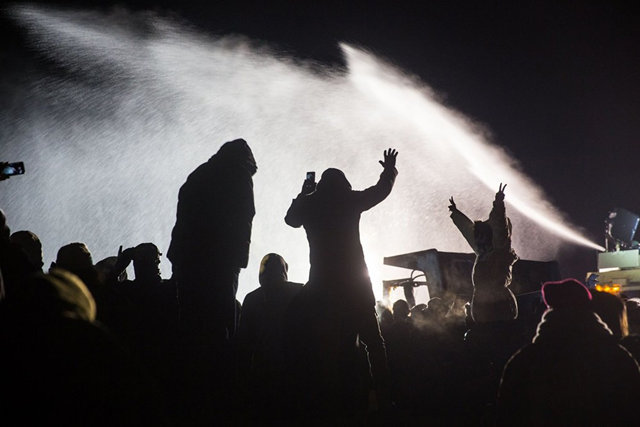 In below-freezing weather on 20 November 2016, law enforcement deployed tear gas, water cannons, percussion grenades, and rubber bullets against hundreds protesting the Dakota Access Pipeline. News reports confirm more than 300 people have been injured. Many were knocked to the ground after being hit in the head by rubber bullets. One woman may lose her arm. Photo: Sacred Stone Camp