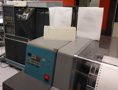 "A greeting card with a tree and ""Ho Ho Ho"" inside, created on the vintage 1401 mainframe. The cards are on top of the 1403 line printer, and the 1401 mainframe is in the background."