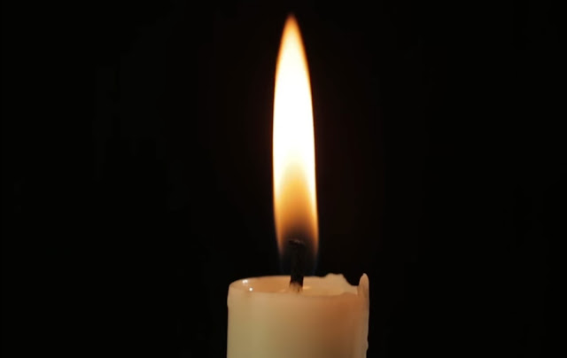 dark cone into the flame of candle, around the wick.