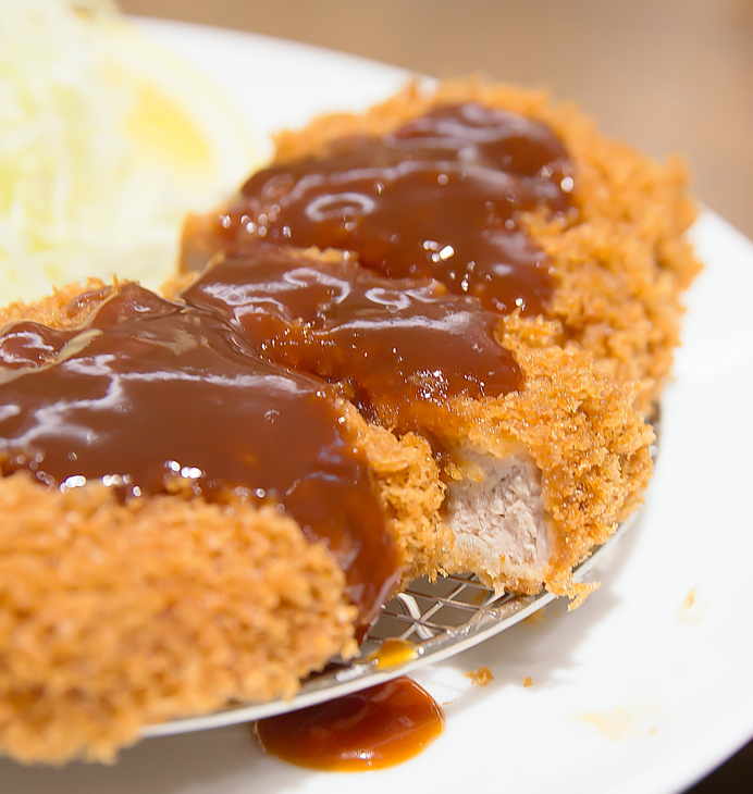 close-up photo of breaded pork with sauce on top