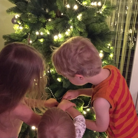 Geschwister schmücken den Weihnachtsbaum gemeinsam