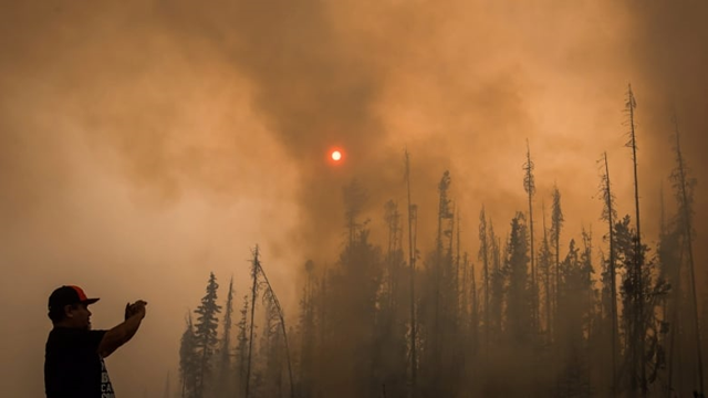 In this 15 August 2018 photo, Verne Tom photographs a wildfire burning along a logging road approximately 20 kilometres southwest of Fort St. James. 2018 was the worst year on record for wildfires in B.C. Photo: Darryl Dyck / Canadian Press