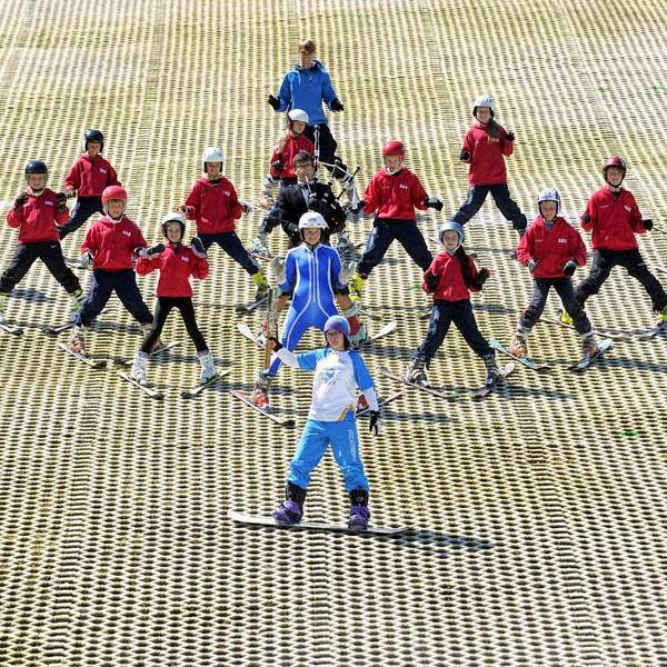 A Commonwealth Games baton bearer leads a procession down an artificial ski slope in Glasgow on July 22, 2014, ahead of the opening of the 2014 Commonwealth Games in the city of July 23, 2014.