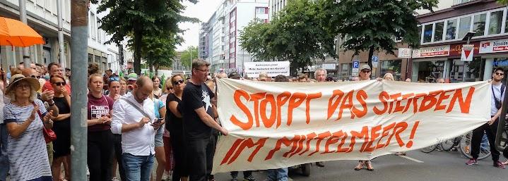 Demonstrant*innen, Transparent: «Stoppt das Sterben im Mittelmeer!».