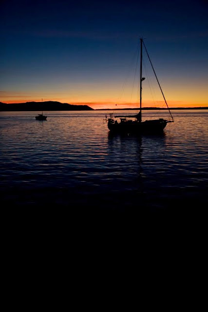 A sailboat glides effortlessly through the waters of peaceful, picturesque Bellingham Bay, where the changing colors of each Bellingham sunset paint golden light onto the historic city, majestic mountains and quaint San Juan Islands.Credit: Peter James