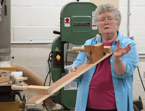 Photo: The band saw is a very dangerous tool. Keep your hands away! Margaret shows a sled for holding oddly shaped pieces safely...