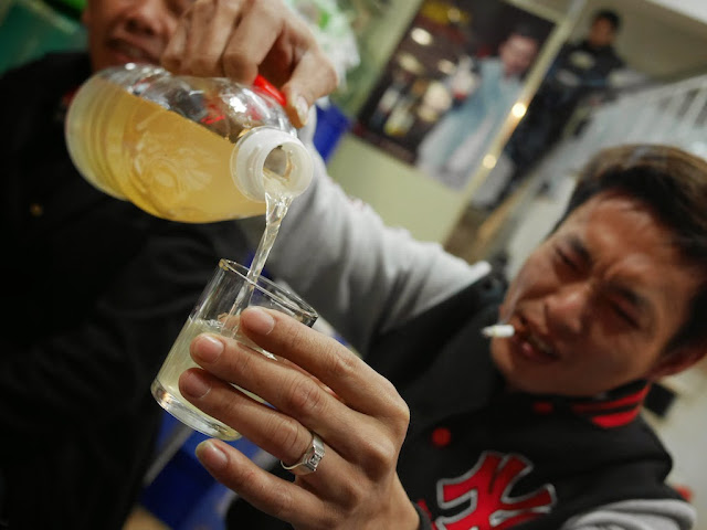 man pouring mijiu into a glass at a restaurant in Xiamen