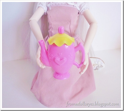 A doll holding the tea pot to show off the pretty design.  It is pink with a yellow lid and has a heart shapes and flowers on it.