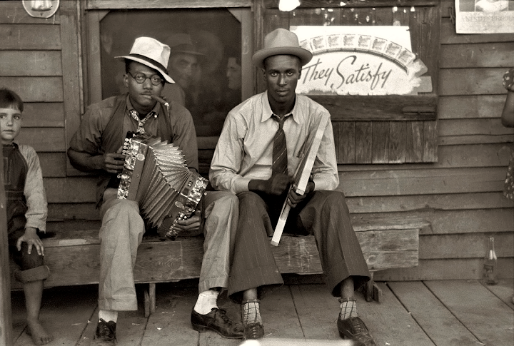 Creole musicians playing an accordion and a washboard in front of a store, near New Iberia, Louisiana (1938).