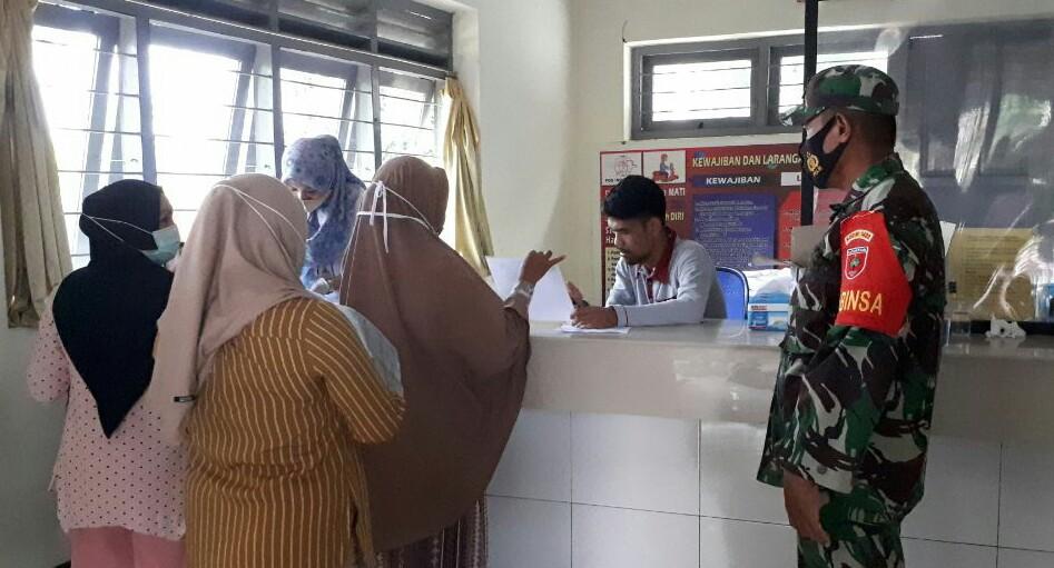 Kawal Penyaluran Bantuan Sosial Tunai, Babinsa 05 Marioriwawo Siaga di Kantor Pos Takalala