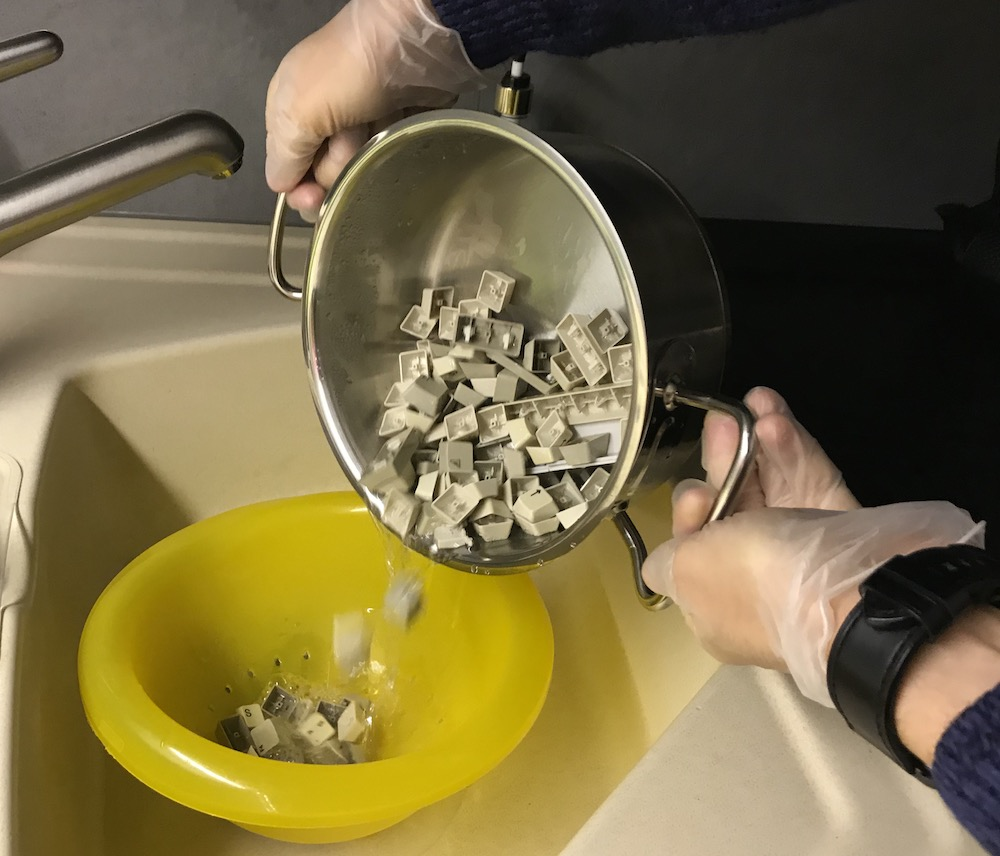 Key caps being poured into a sieve, for rinsing.