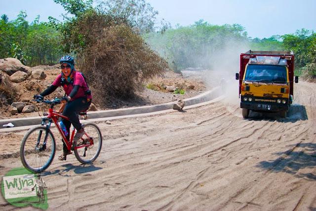 pesepeda bersepeda melibas medan jalan berdebu vulkanik menuju Mata Air Bebeng di Glagaharjo