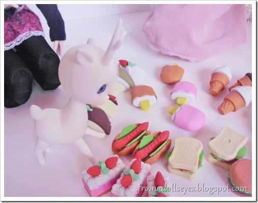 A small deer doll staring at the assortment of food shaped erasers.