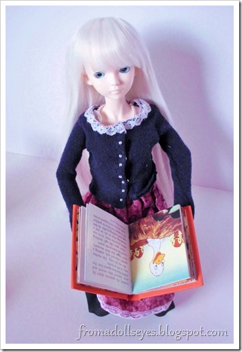 A ball jointed doll reading a small book, bought at a thrift store.