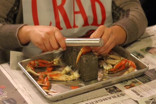 120511,  JB :   An aluminum cracking tool and a brick work much better than traditional nut cracking tools.  Student learn the correct method to crack crab during a crab cracking class by Jon Rowley at Taylor Shellfish Store in Seattle, WA, Monday December 05, 2011.  (Jim Bates / THE SEATTLE TIMES)   116947 JB: JON ROWLEY TEACHES A CLASS ON THE PROPER WAY CRACK A CRAB AT TAYLOR SHELLFISH MARKET