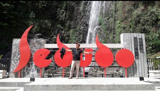 Berfoto di anak tangga dengan background tulisan Sedudo