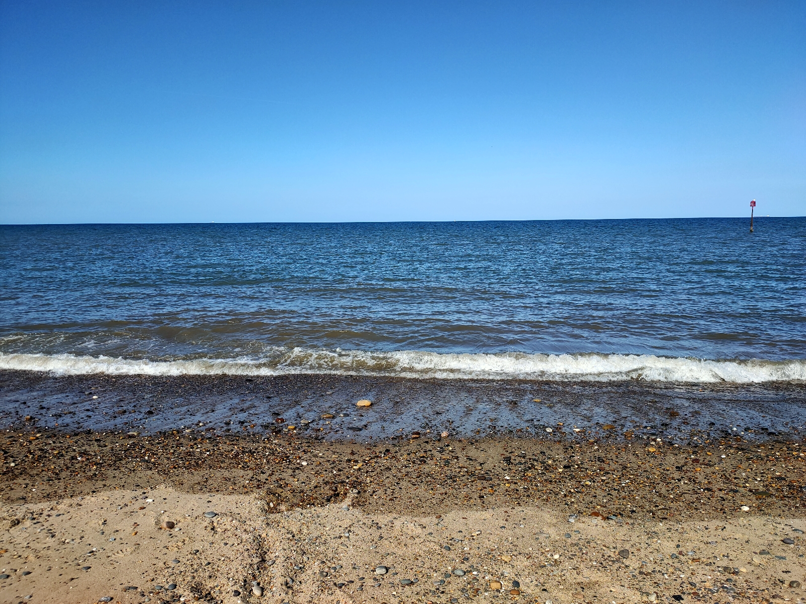 A beach, looking out to sea. Bright blue skies.
