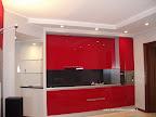 cucina laccata rossa con ribassamento in cartongesso con faretti, a sinistra l'ingresso con mensole in vetro