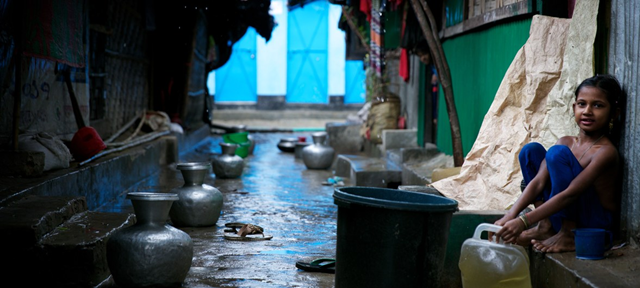 A Rohingya refugee child sits next to buckets collecting rainwater at a makeshift refugee camp in Cox's Bazar, Bangladesh. With the arrival of rains, the challenges have multiplied for hundreds of thousands of refugees in the area. Photo: Sujan / UNICEF
