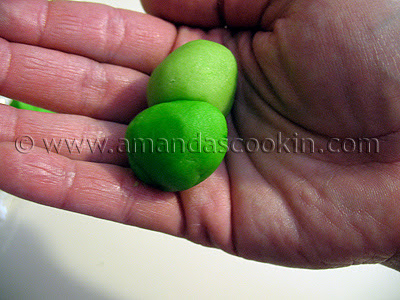 A photo of two balls of green St. Patrick\'s day cookie dough in a palm.