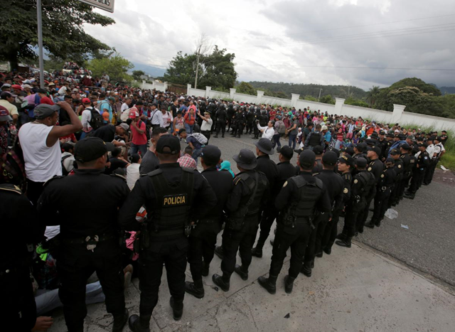 Guatemalan police officers watch as Honduran migrants, part of a caravan trying to reach the U.S., arrive in Esquipulas city in Guatemala, 15 October 2018. Photo: Jorge Cabrera / REUTERS