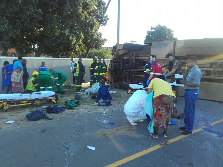 Paramedics attend to injured workers after a County Fair staff bus that overturned in Cape Town on Thursday.