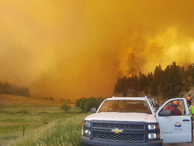 A fire crew stands with their truck near a forest fire in British Columbia, 22 July 2017. Hills firey are lending a hand to put out Canadia forest fires. Photo: Erica Roy / ibusinesslines