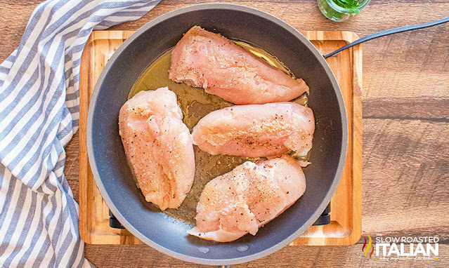chicken breasts fried in a skillet with oil
