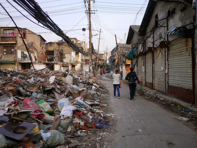 two women walking by rubble near Beizheng Street in Changsha