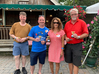 Corcoran Management Company employees holding their mini trophies for golfing at Kimball Farm