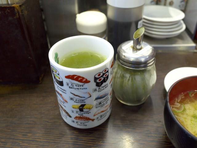 湯呑みに入れたお茶と、お茶の素の粉末のボトル