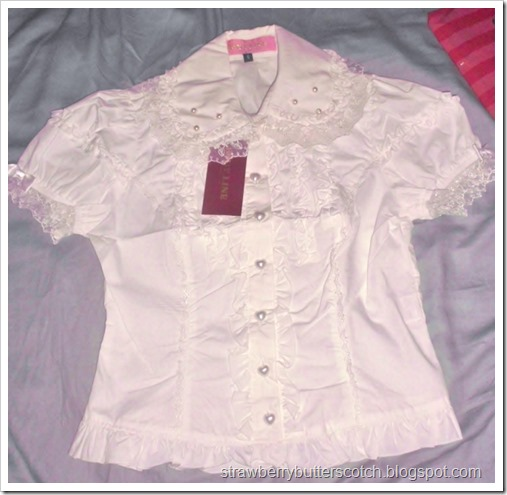 Blouse l364 from Bodyline, before a little alteration.  It has puffed sleeves with bows, heart shaped buttons, ruffles down the front, and a peter pan collar trimmed with faux pearls and lace.  A great blouse for lolita fashion.