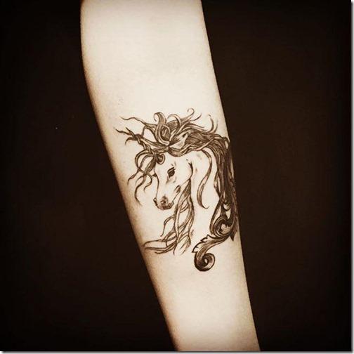 tatuaje_de_unicornio_en_tonos_de_gris_en_el_brazo