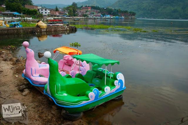 Dua buah perahu kayu berbentuk anjing laut teronggok di pinggir Danau Toba di kota Parapat, Sumatera Utara karena rusak dan sepi peminat