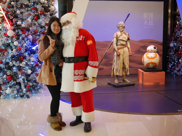 young woman posing for a photo with Santa Claus in front of Star Wars display at the IAPM shopping center in Shanghai