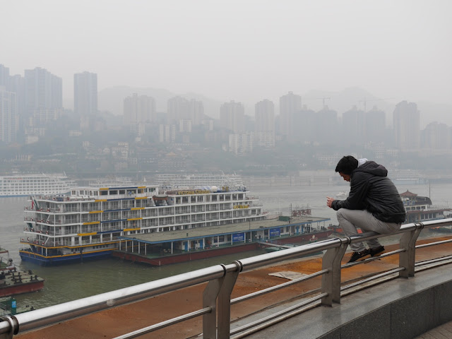 young man sitting on a railing while talking a mobile phone