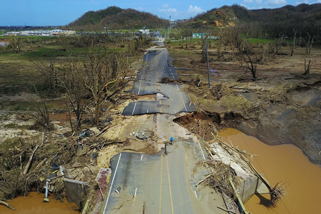 A man rides his bicycle through a damaged road in Toa Alta, west of San Juan, Puerto Rico, on 24 September 2017, following the passage of Hurricane Maria. Photo: Ricardo Arduengo / AFP / Getty Images