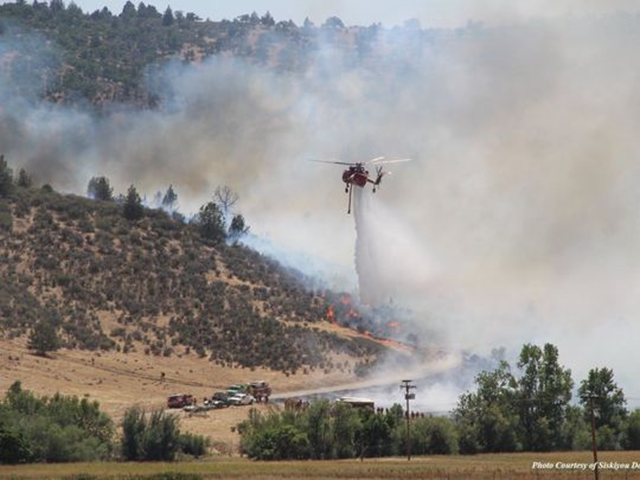 A helicopter crew drops water on a section of the Klamathon Fire burning near the California-Oregon border, 5 July 2018. Photo: California Department of Forestry and Fire Protection