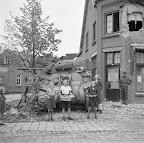 Children bringing apples to the crew of a Sherman tank from the 2nd Armoured Battalion Irish Guards at Aalst. In the back a bakery with huge battle damage. Date: September 18, 1944. Photographer: Willem van de Poll. Source: Dutch National Archive