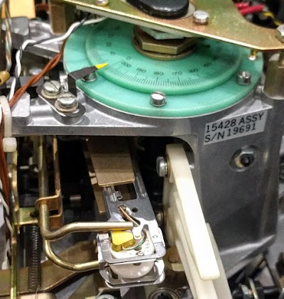 The green head positioner transducer provides feedback to the head servo mechanism. The pointer and dial indicate what track the heads are on.
