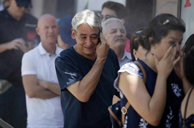 Humberto Berlanga, center, wipes sweat from his face while waiting in the heat in line at the Gold & Silver Pawn shop, Tuesday, 24 July 2018, in Las Vegas. The National Weather Service has issued an excessive heat warning for the Las Vegas valley. Photo: John Locher / Associated Press